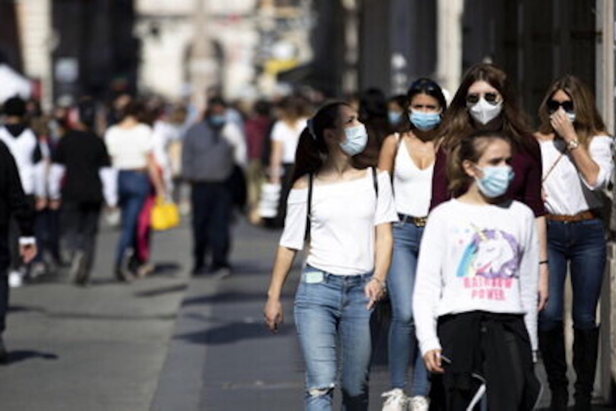 Giovani ragazzi passeggiano con le mascherine