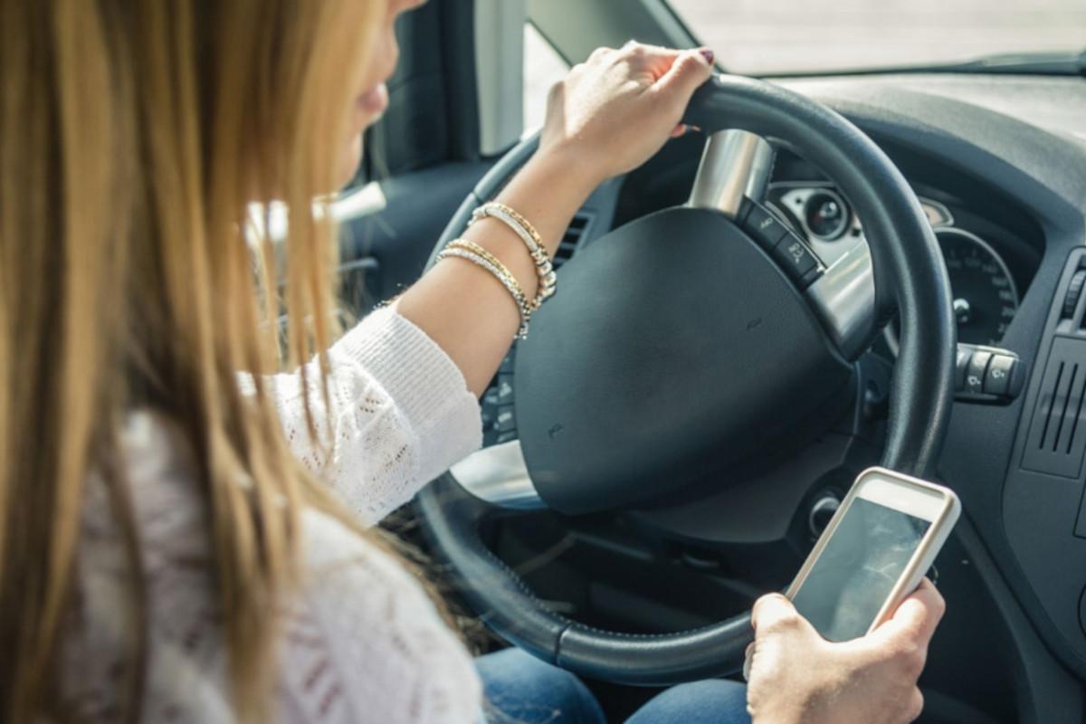 donna in auto fa uso del cellulare