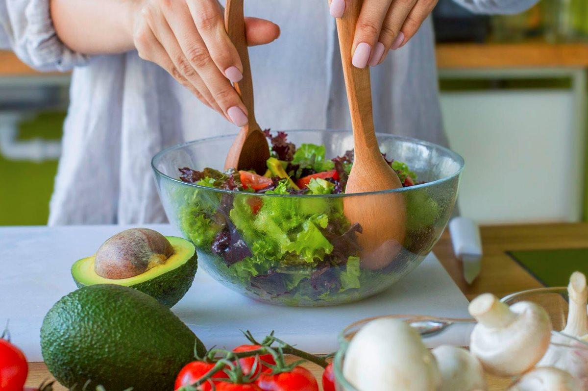 Dieta alimentare, donna che condisce un'insalata
