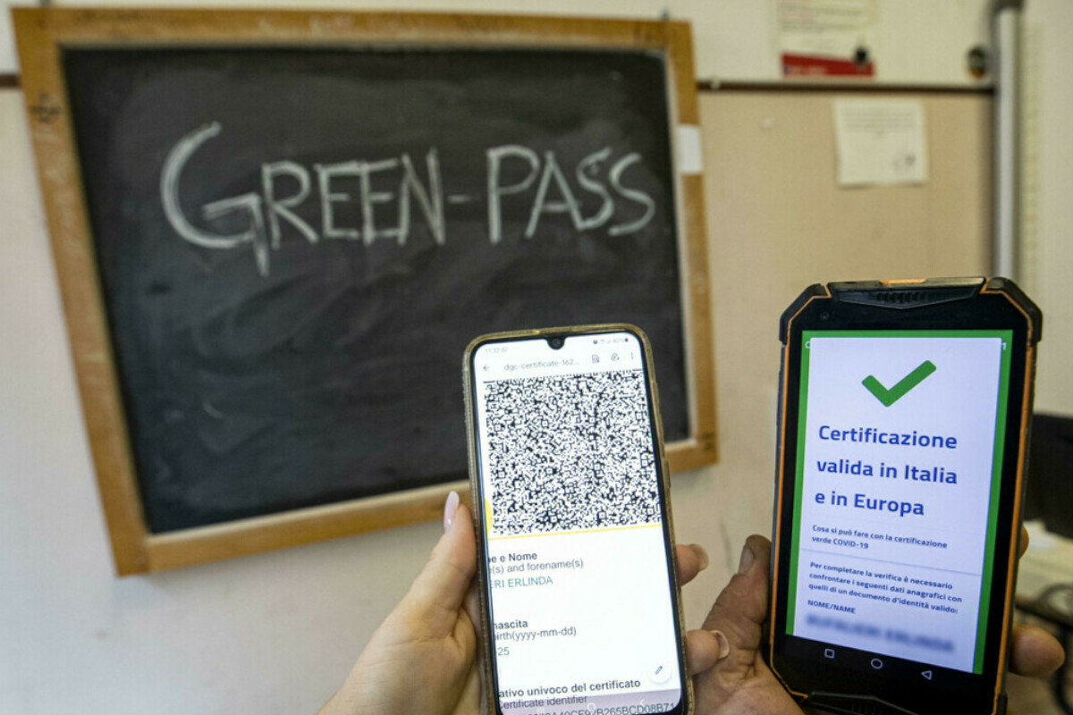 Una lavagna con scritto Green Pass sullo sfondo